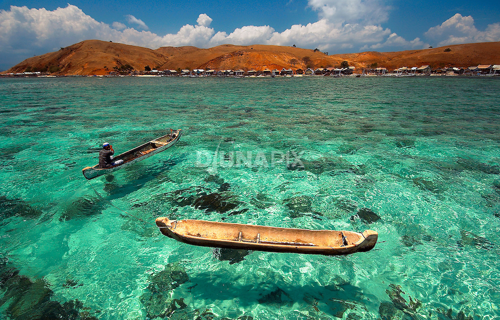 Clear aqua waters, dug out canoe, red island, PapagaranKomodo National Park