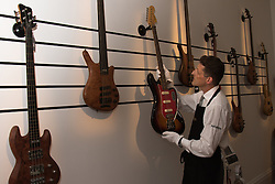 London, September 24th 2015. A Sotheby's Gallery Technician arranges a display of basses owned by Cream's Jack Bruce.  They feature in the auctioneers Rock and Pop exhibition running 24th - 28th September ahead of an auction on September 29th. The exhibition gathers together lyrics, instruments, stage costumes and artworks from some of the world's greatest pop and rock performers and groups, including Abba, The Beatles, Bob Dylan, Pink Floyd and Bruce Springsteen.
