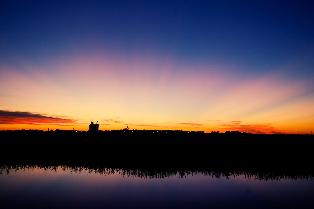 With the sun below the horizon, rays of light beam out over the Nebraska plains in a riot of colors. The sky is also reflected in a small farm pond here west of Lincoln, NE.