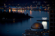 Illuminated Olympic rings float on a barge in Burrard Inlet at dusk Tuesday evening with Vancouver's famous Stanley Park looming on the left.