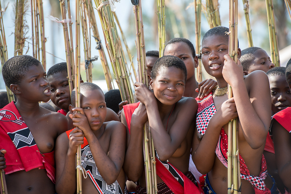 Portraits of Young Women at the Reed Dance-Ludzidzini, Swaziland, Africa - The Swazi Umhlanga, or reed dance ceremony, 100,000 unmarried women , or maidens, celebrate their virginity by bringing reeds for the Swazi Queen Mother's Kraal during this 8 day long annual tradition and dancing in a massive gathering before King Mswati III, the royal family, and the public.