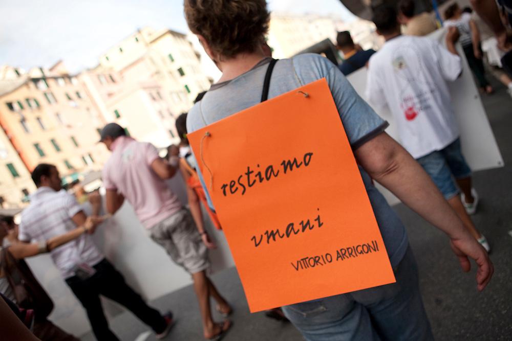 Genova, 23 luglio 2011. Manifestazione in ricordo dei fatti del G8 di dieci anni prima. Manifestante con una citazione di Vittorio Arrigoni, l'attivista italiano ucciso in Palestina pochi mesi prima.