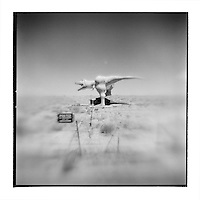 USA, Arizona, Holbrook, Blurred black and white image of Dinosaur sculptures in desert along Route 66 with No Trespassing sign and road cattle guard