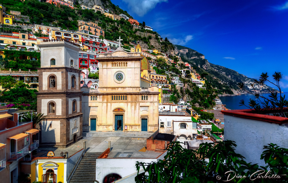 """""""Colorful overview of Santa Maria Assunta in Positano""""...<br /> <br /> After an exhilarating drive along the high cliffs on the Amalfi coast from Sorrento down to Positano, I found myself in sensory overload with its beauty and photogenic appeal. After circling around the entire village and its cliffside three times on Positano's only street, which was a single lane winding down from the top and back up and over to where I began, I finally found the parking garage by the hotel, about 2/3rds up the facing village in this image. The climb down the winding road and steep staircases made for quite a workout in the hot late May sun. Reaching the beach and marina, I forgot about my exhaustion and could not capture enough of Positano's plush beauty; however, the large amount of tourists and bright sun did not allow for ideal conditions. As I made my way along the beach and shoreline, rays from the late afternoon sunlight coming over the mountain top blinded me as they illuminated the famous church. The Church of Santa Maria Assunta is a prominent aspect of Positano's cultural, religious and architectural landscape. Strategically located in the center of town with the backdrop of the azzurro Mediterranean Sea, the church's colorful majolica tiled cupola is one of the town's iconic symbols. The ancient church was dedicated to the Blessed Virgin Mary in 1159. Santa Maria keeps a blessed and watchful eye over Positano and welcomes all to this beautiful seaside village."""