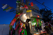 A young woman ties a wish to a bamboo sprig wish tree outside a fire station during the Tanabata matsuri in Fussa,, Tokyo, Japan. Sunday August 7th 2016. The Tanabata or star festival is usually celebrated in July though early August more closely follows the traditional calendar. Wishes are tied to wish trees set up in streets and other public places and some areas hold large street parties and parades. The Fussa Tanabata matsuri was started in 1951.