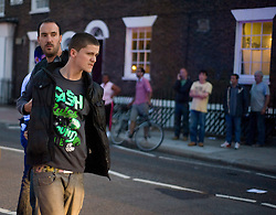 Picture by Mark Larner. Picture shows locals looking on as police arrest a youth near Clapham Junction after witnesses reported seeing him with a baseball bat. 09/08/2011.