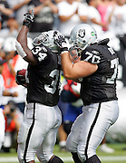 OAKLAND, CA - OCTOBER 2:  Running back LaMont Jordan #34 of the Oakland Raiders points skyward as he celebrates with teammate Brad Badger #70 after Jordan scores on a 2 yard touchdown run for a 10-0 lead over the Dallas Cowboys in the first quarter at McAfee Coliseum in Oakland, California on October 2, 2005. The Raiders defeated the Cowboys 19-13. ©Paul Anthony Spinelli *** Local Caption *** LaMont Jordan;Brad Badger