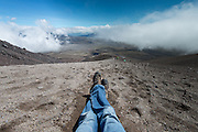 A man sitting down with legs crossed on the slopes of Cotopaxi volcano, Ecuador.