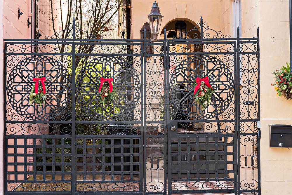 A wrought iron garden gate of a historic home decorated with Christmas wreaths on Meeting Street in Charleston, SC.
