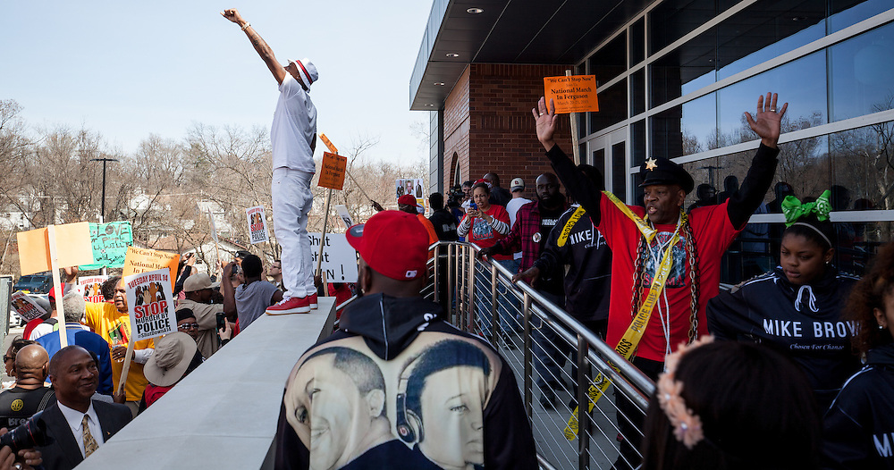 Activist leader DONTE CARTER, holding his fist in the air, speaks to a large crowd of protesters gathered in front of the Ferguson police station.