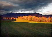 Sunlight illuminating Mt. Mansfield Vermont under dark Storm clouds