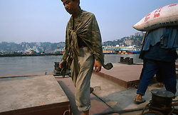 CHINA SICHUAN PROVINCE CHONGQUING MAY99 - Dockworkers carry goods from a ferry at the shore of the Yangtse river where it merges with the Jailing river at Chongquing. Seven large cities, including Chongquing, and thousands of villages will be submerged once the water level rises after the completion of the controversial Three Gorges Dam project further downriver. The flooding of areas reaching back more than 550Km upriver will require the evacuation and resettlement of more than 10 million people.  jre/Photo by Jiri Rezac