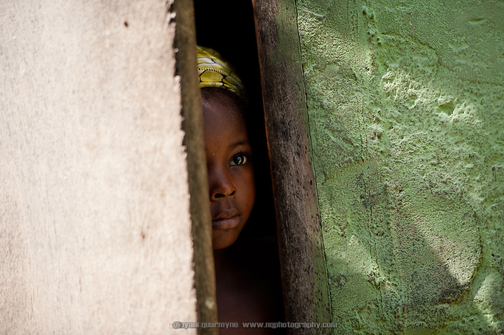 A girl peeps out from a doorway in Avenor, a slum in Ghana's capital, Accra.