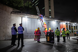 © Licensed to London News Pictures. 01/09/2019. Manchester, UK. Firefighters are called after police , concerned for safety, refuse to allow the use of shorter ladders , used by the activists to access the rooftop . Several dozen police intervene after Extinction Rebellion supporters climb on to the roof and drop a banner from cafes in Piccadilly Gardens as roads around Deansgate remain closed to traffic by environmental campaigners . One of the protesters, dressed as Spiderman , is understood to be Kevin Charles Godin-Prior . Manchester City Council has declared a climate emergency but activists say the council's development plans do not reflect this . Photo credit: Joel Goodman/LNP