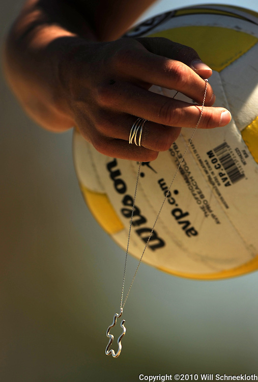 AVP beach volleyball player Cayley Thurlby dangles her necklace from her fingers after losing and then recovering it while scirimmaging at the beach volleyball pits at California State University Long Beach in Long Beach, CA on April 8, 2010.
