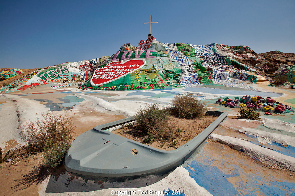 Leonard Knight's folk art and religious creation in the desert of Niland, CA. near the Salton Sea. Leonard Knight created the mountain in 1984 by stacking junk and local debris, then covering it with cement and thick paint. Knight now uses a hay adobe and covers it with household paint. The mountain now reaches 50 foot high by 150' wide. Salvation Mountain is dedicated to Knight's love for Jesus and God. Many Christian and religious passages can be seen written on and inside the mountain.