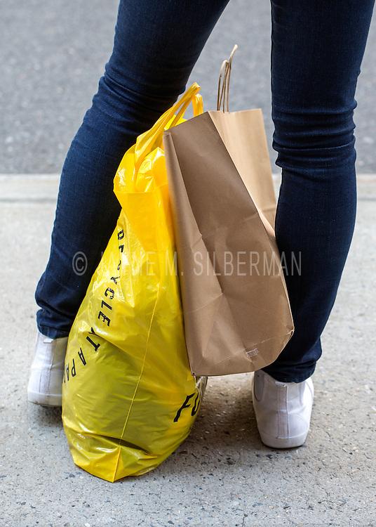 A female shopper waits at a city bus stop.