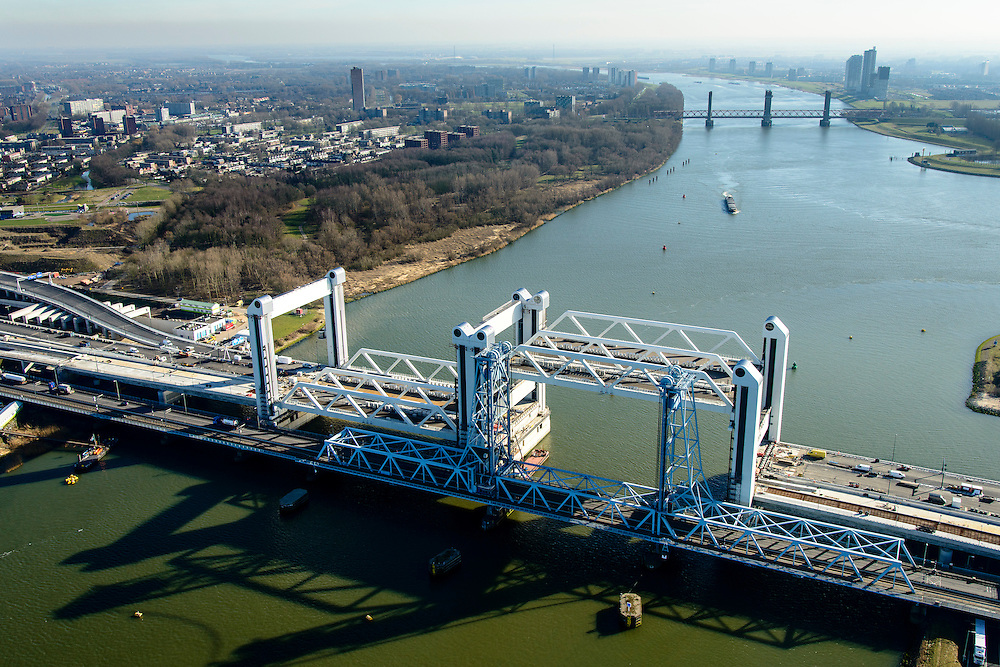 Nederland, Zuid-Holland, Rotterdam, 18-02-2015; bouw van de nieuwe Botlekbrug.<br /> De brug over de Oude Maas is een hefbrug, een van de twee brugdelen in geheven toestand. De oude brug met heftorens in de voorgrond, Spijkenisserbrug in het verschiet.<br /> Construction of the new Botlek bridge.<br /> The bridge over the Oude Maas is a vertical-lift bridge or lift bridge, one of the two bridge sections raised. <br /> luchtfoto (toeslag op standard tarieven);<br /> aerial photo (additional fee required);<br /> copyright foto/photo Siebe Swart