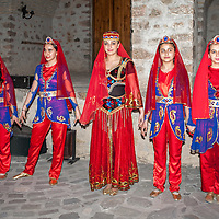 Young town girls dressed in folkloric outfits take a standing ovation after a short performance at the Sheki Caravan Saray