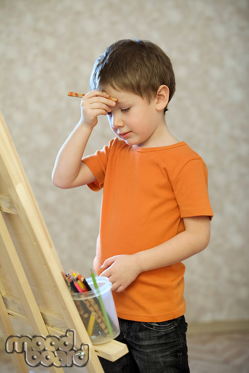 A young boy holding his hand with a pencil in up to his face  standing infront of a canvas with a pot of coloured pencils