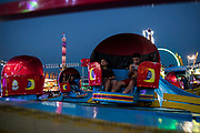 WASHINGTON, USA - August 19: Two boys, one checking his phone, spin around on an amusement ride at the Montgomery County Agricultural Fair in Gaithersburg, Md., USA on August 19, 2017.