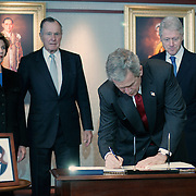 """Pres. Bush, First Lady Laura Bush, former Presidents George H.W. Bush and William Jefferson Clinton, sign a book of condolences at the Embassy of Thailand  Monday, January 3, 2005.  The photo on the table is that of Khun Poom Jensen, grandson of the King of Thailand.  President Bush told reporters at the White House, """"I have asked two of America's most distinguished private citizens to head a nationwide charitable fund-raising effort.""""..Photo by Khue Bui"""