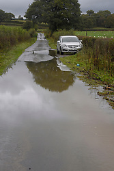 © Licensed to London News Pictures. 11/10/2019. Llandrindod Wells, Powys, Wales, UK. A road is flooded as a stream burst it's banks near Llandrindod Wells in Powys, UK. after heavy rainfall hits Powys this morning. Photo credit: Graham M. Lawrence/LNP