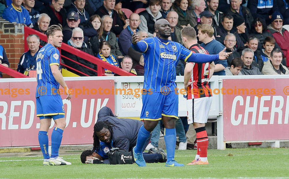 Bayo Akinfenwa of Wimbledon calls for a stretcher for the injured Andy Barcham during the Sky Bet League 2 match between AFC Wimbledon and Morecambe at the Cherry Red Records Stadium in Kingston. October 17, 2015.<br /> Simon  Dack / Telephoto Images<br /> +44 7967 642437