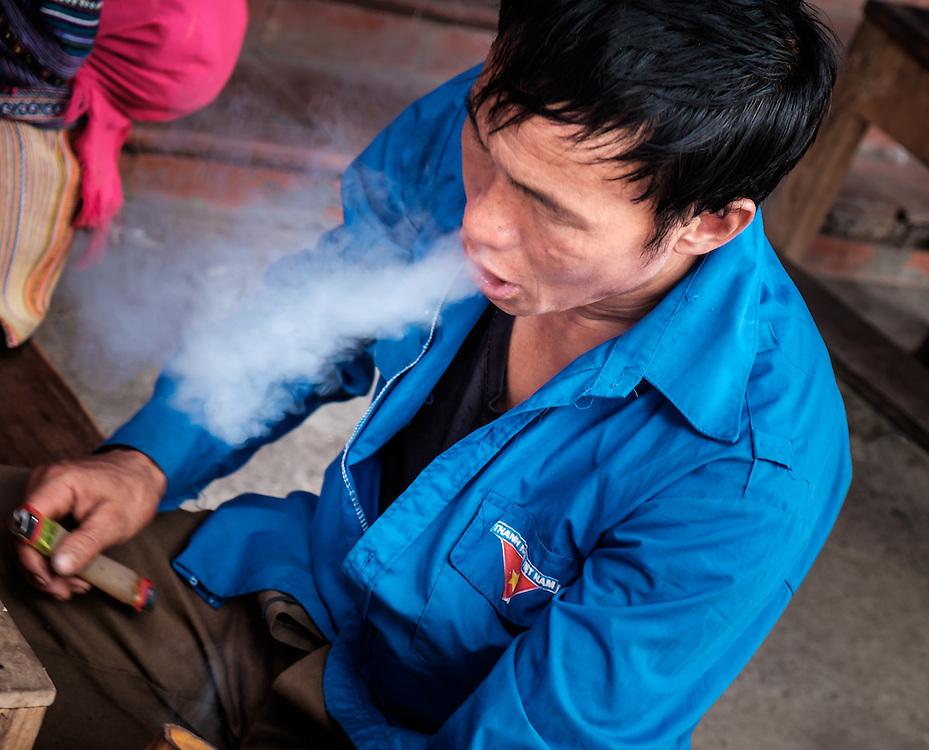 BAC HA, VIETNAM - CIRCA SEPTEMBER 2014:  Vietnamese man smoking at the Bac Ha sunday market, the biggest minority people market in Northern Vietnam