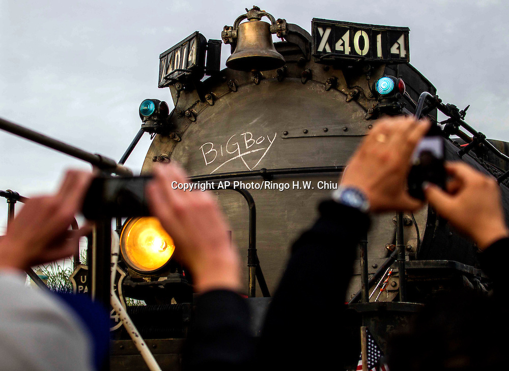 Spectators rise the mobile phone and take pictures the historic locomotive, Union Pacific Big Boy No. 4014 at Metrolink Station in Covina, Calif., on Sunday, Jan., 26, 2014. The locomotive will head for Colton over the next several weeks before No. 4014 departs for Union Pacific's Heritage Fleet Operations headquarters in Cheyenne, Wyo.. The Union Pacific Big Boy No. 4014 is one of the most famous locomotives in the world today. It is the heaviest single expansion steam locomotive ever built, weighing about 1,200,000 pounds. The Big Boy class was designed for heavy freight service and was used between Ogden, Utah, and Cheyenne, Wyo. Built in 1941, No. 4014 was retired in 1959 after only 18 years of service. No. 4014 arrived at the Pomona Fairgrounds in January 1962. In the summer of 2013, Union Pacific reacquired Big Boy No. 4014 and plans to restore it for operation as part of its world renowned steam program. (AP Photo/Ringo H.W. Chiu)