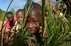 Children pretend they are lions waiting to eat a villager in the village of Simana, Tanzania. Ami Vitale