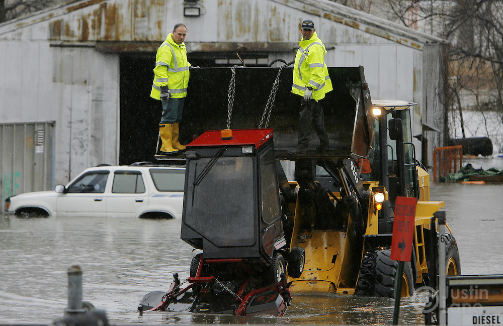 Workers at the Department of Public Works in Teaneck, New Jersey remove equipment from a flooded lot on Monday 16 April 2007. A large storm delivered records amount of rain to the East Coast of the United States over the weekend and today causing flooding and other weather related problems.