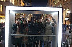© Licensed to London News Pictures. 14/01/2016. London, UK. Visitors to Lumiere London photograph a giant illuminated net sculpture entitled '1.8 London' as it hangs above Oxford Circus. Lumiere London is a major new light festival that, over four evenings, brings together<br /> some of the world's most exciting artists working with light utilising large-scale video-mapped projections, interactive pieces and installations. Photo credit: Peter Macdiarmid/LNP