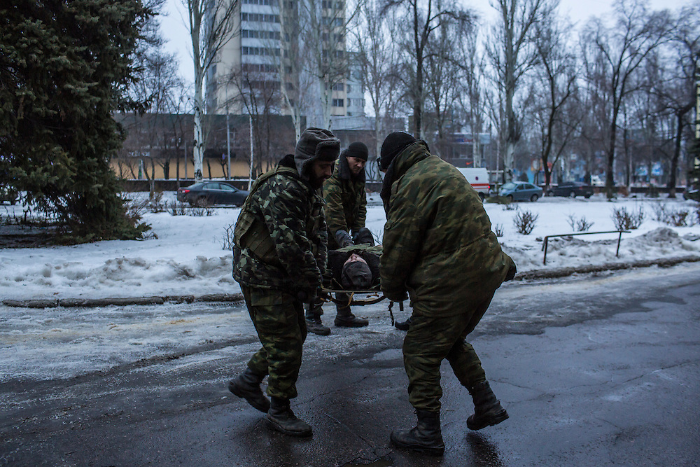 DONETSK, UKRAINE - JANUARY 23, 2015: The body of a rebel fighter who was killed is unloaded from a truck at Vishnevskogo Hospital by other rebel fighters in Donetsk, Ukraine. After the rebels finally took control of the heavily contested airport in Donetsk from the Ukrainian Army, they have promised an offensive to extend their territory further. CREDIT: Brendan Hoffman for The New York Times