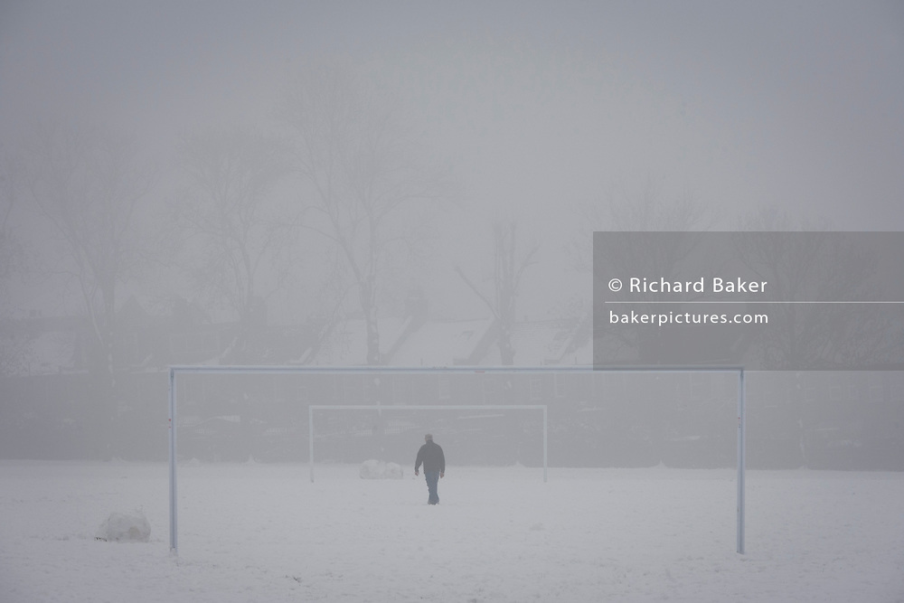 Seen through two goalposts, a lone person walks over a snowbound football pitch in a local park. During a prolonged cold spell of bad weather, snow fell continuously on the capital days before, allowing families the chance to enjoy the bleak conditions in Ruskin Park in the borough of Lambeth.