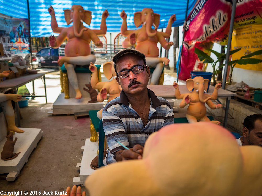 """09 SEPTEMBER 2015 - BANGKOK, THAILAND:  A craftsman at the Vishnu Temple in Bangkok works on a statue of Ganesha, an important Hindu deity known as the """"overcomer of obstacles."""" Ganesha Chaturthi is the Hindu festival celebrated on the day of the re-birth of Lord Ganesha, the son of Shiva and Parvati. Ganesha is widely revered as the patron of arts and sciences and the deva of intellect and wisdom. The last day of the festival is marked by the immersion of the deity in nearby bodies of water. The immersion symbolizes the cycle of creation and dissolution in nature. The deities made at the Vishnu Temple in Bangkok will be submerged in rivers and streams across Thailand at several Ganesha festivals held in September.        PHOTO BY JACK KURTZ"""
