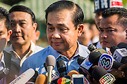 "11 JANUARY 2014 - BANGKOK, THAILAND: General PRAYUTH CHAN-OCHA, Commender in Chief of the Thai Royal Army, answers reporters' questions during a Children's Day fair in Bangkok. The Royal Thai Army hosted a ""Children's Day"" event at the 2nd Cavalry King's Guard Division base in Bangkok. Children had an opportunity to look at military weapons, climb around on tanks, artillery pieces and helicopters and look at battlefield medical facilities. The Children's Day fair comes amidst political strife and concerns of a possible coup in Thailand. Gen Prayuth has issued mixed signal on a coup at one point saying there wouldn't be one, and later saying he wouldn't talk about a possible coup. Earlier in the week, the Thai army announced that movements of armored vehicles through Bangkok were not in preparation of a coup, but were moving equipment into position for Children's Day.      PHOTO BY JACK KURTZ"