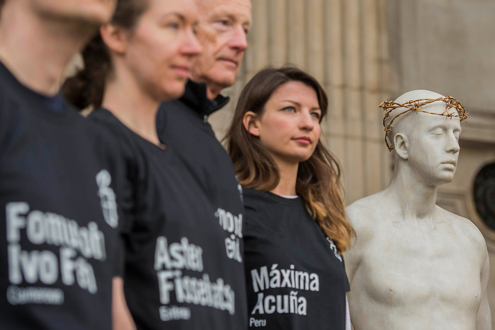 "Amnesty staff with victims names on their t-shirts - Kate Allen, Director of Amnesty International UK, helped by Canon Mark Oakley (Chancellor of St Paul's Cathedral), installs Mark Wallinger's 'Ecce Homo' statue at St Paul's Cathedral. The life-size sculpture shows the figure of Jesus Christ and was the first artwork to be shown on Trafalgar Square's fourth plinth in 1999.Mark Wallinger, who won the Turner Prize in 2007, said: ""This vulnerable figure will stand at the top of the steps outside the entrance to St Paul's Cathedral as we approach Easter to highlight the plight of people around the world who are imprisoned and whose lives are threatened for speaking the truth, and for what they believe."""