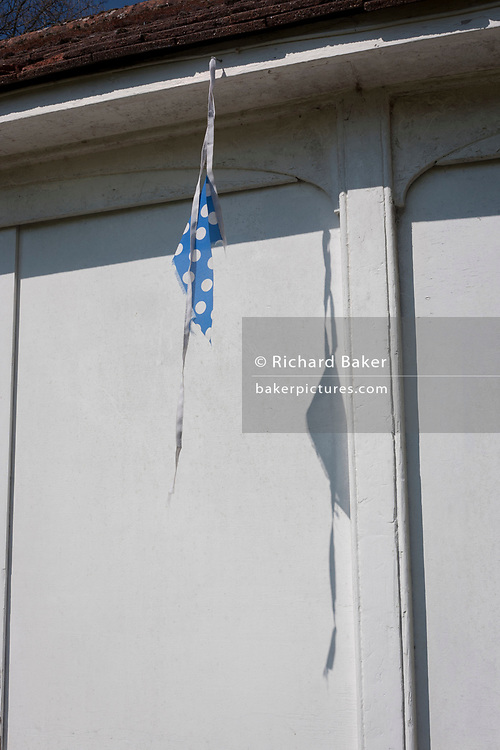 Sad spotted bunting hanging from a cricket pavillion, on 3rd April, 2017, in Hadlow, Kent, England.