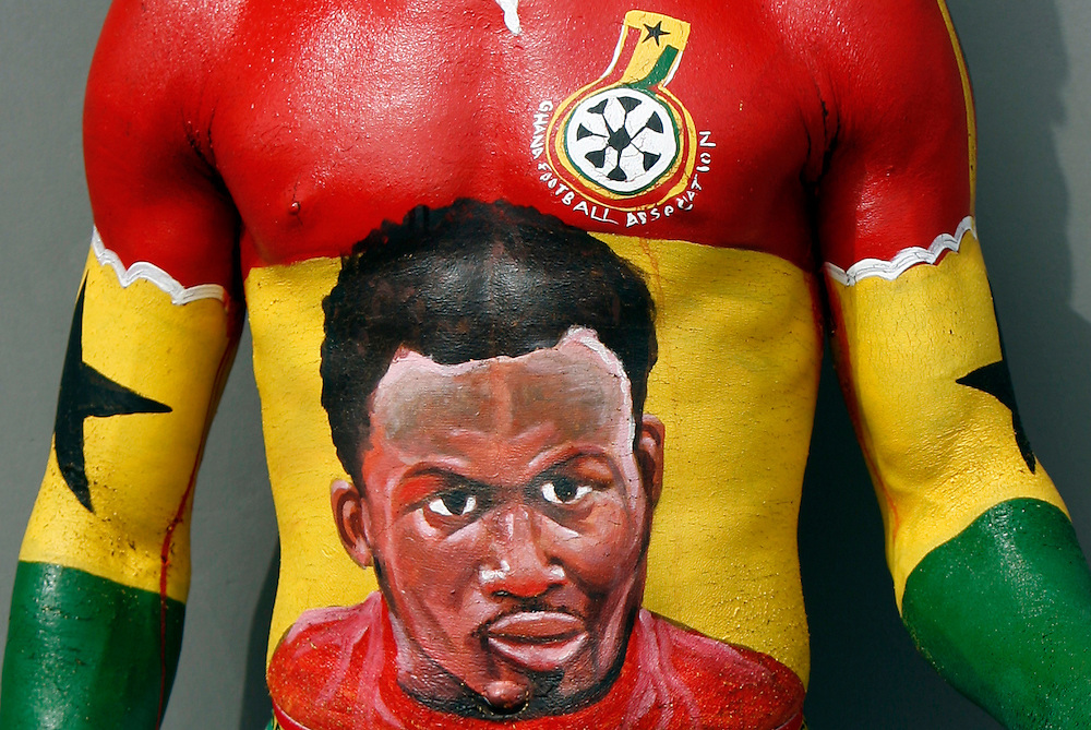 Ghana Fan in full body paint with a picture of Micheal Essien painted on his belly. He is busking for tips by posing with other fans for photos. Fans and supporters. Ghana V Nigeria in the Quarter final of the African Cup nations 2008. Ohene Djan stadium. Accra. Ghana. West Africa.