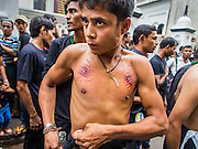 04 NOVEMBER 2014 - YANGON, MYANMAR: Burmese men prepare to flagellate themselves with chains and razors in front of Mogul Mosque (Masjid) on Ashura in Yangon. The flagellation shows solidarity with Hussein and his family. Mogul Mosque is the principal Shia mosque in Yangon. Ashura commemorates the death of Hussein ibn Ali, the grandson of the Prophet Muhammed, in the 7th century. Hussein ibn Ali is considered by Shia Muslims to be the third imam and the rightful successor of Muhammed. He was killed at the Battle of Karbala in 610 CE on the 10th day of Muharram, the first month of the Islamic calendar. According to Myanmar government statistics, only about 4% of the population is Muslim. Many Muslims have fled Myanmar in recent years because of violence directed against Burmese Muslims by Buddhist nationalists.     PHOTO BY JACK KURTZ