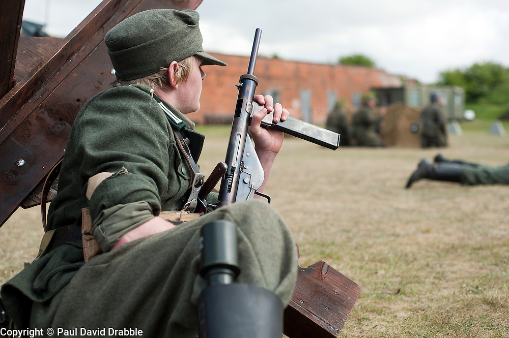 Reenactor portraying a Gro&szlig;deutschland Panzer Grenadier takes cover behind a tank trap during a battle reenactment at Fort Paull <br /> 2 May 2011<br /> Image &copy; Paul David Drabble