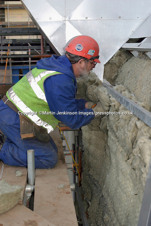 Contruction worker fixing insulation to trunking during the installation of flue gas desulpherisation at a coal fired power station.