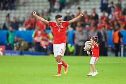 LILLE, FRANCE - Friday, July 1, 2016: Wales' Neil Taylor celebrates the 3-1 victory against Belgium at full time with his young daughter on the pitch after the UEFA Euro 2016 Championship Quarter-Final match at the Stade Pierre Mauroy. (Pic by Paul Greenwood/Propaganda)