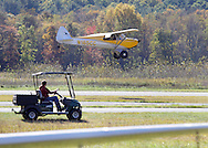 Wurtsboro, New York - A single-engine plane comes in for a landing as an employee in a golf cart looks on during a fly-in at Wurtsboro Airport on Oct. 9, 2010.