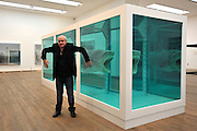 © Licensed to London News Pictures. 02/04/2012. London, UK . Damien Hirst stands in front of 'The Physical Impossibility of Death in the Mind of Someone Living 1991, a 14 ft. shark suspended in formaldehyde. The Tate Modern presents the first substantial retrospective of British artist Damien Hirst. The exhibition tuns 4th April - 9th September at Tate Modern London. Photographers Stephen Simpson/LNP