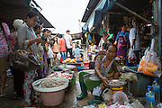 A Thai woman buys prawns from a vendor at the Maeklong railway market.