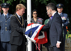 © licensed to London News Pictures. CARTERTON, UK.  01/09/11. The Town Mayor of Wootton Bassett, Cllr Paul Heaphy hands over the flag to the Chairman of Brize norton Parish Council Cllr Keith Glazier and the Deputy Mayor of Carterton Cllr Adrian Coomber. A ceremony, attended by British Prime Minister David Cameron,  takes place at The Memorial Garden at Norton Way in Carterton, Oxfordshire today (01 Sept 2011). The Garden will become the focal point during the repatriation of UK service personnel from RAF Brize Norton. The Union Flag that used to fly at repatriations in Wooton Bassett was handed over and was blessed. . Mandatory Credit Stephen Simpson/LNP