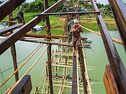 17 SEPTEMBER 2014 - SANGKHLA BURI, KANCHANABURI, THAILAND: Thai soldiers and members of the Mon community work on the repair of the Mon Bridge. The 2800 foot long (850 meters) Saphan Mon (Mon Bridge) spans the Song Kalia River. It is reportedly second longest wooden bridge in the world. The bridge was severely damaged during heavy rainfall in July 2013 when its 230 foot middle section  (70 meters) collapsed during flooding. Officially known as Uttamanusorn Bridge, the bridge has been used by people in Sangkhla Buri (also known as Sangkhlaburi) for 20 years. The bridge was was conceived by Luang Pho Uttama, the late abbot of of Wat Wang Wiwekaram, and was built by hand by Mon refugees from Myanmar (then Burma). The wooden bridge is one of the leading tourist attractions in Kanchanaburi province. The loss of the bridge has hurt the economy of the Mon community opposite Sangkhla Buri. The repair has taken far longer than expected. Thai Prime Minister General Prayuth Chan-ocha ordered an engineer unit of the Royal Thai Army to help the local Mon population repair the bridge. Local people said they hope the bridge is repaired by the end November, which is when the tourist season starts.    PHOTO BY JACK KURTZ