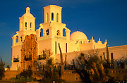 Three-quarter view of Mission of San Xavier del Bac from southeast, golden light of sunrise on wall of adobe, Tucson, Arizona ..Subject photograph(s) are copyright Edward McCain. All rights are reserved except those specifically granted by Edward McCain in writing prior to publication...McCain Photography.211 S 4th Avenue.Tucson, AZ 85701-2103.(520) 623-1998.mobile: (520) 990-0999.fax: (520) 623-1190.http://www.mccainphoto.com.edward@mccainphoto.com.